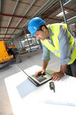 Engineer using laptop computer on construction site — Stock Photo
