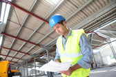 Engineer checking plan in building under construction — Stock Photo
