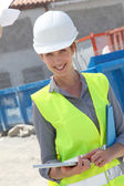 Woman engineer checking building plan on touchpad — Stock Photo