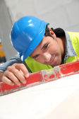 Worker using level on building site — Stock Photo