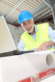 Architect using laptop computer on construction site — Stock Photo