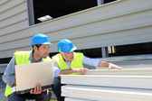 Construction workers checking building material — Stock Photo