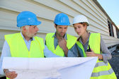 Workteam checking plan on construction site — Stock Photo
