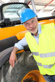Site manager standing by machine — Stock Photo
