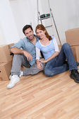 Young couple sitting in their new house — Stock Photo