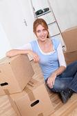 Młoda kobieta siedząca w nowym mieszkaniu — Zdjęcie stockowe