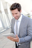 Businessman using electronic tablet outside a building — Stock Photo