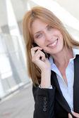 Beautiful saleswoman talking on mobile phone — Stock Photo