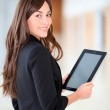 Businesswoman standing in hall with electronic pad — Stock Photo #18225227