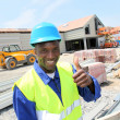 Construction worker on building site with security helmet — Stock Photo #18220597