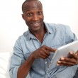 Funny man using electronic tablet at home — Stock Photo #18221345