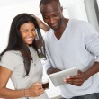 Young couple using electronic pad in kitchen — Stock Photo #18221529