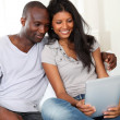 Happy loving couple sitting in sofa with electronic tablet — Stock Photo