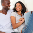 Stock Photo: Happy loving couple sitting in sofwith electronic tablet