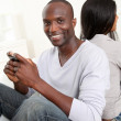 Couple playing with smartphone at home — Stock Photo