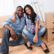 Cheerful couple sitting in empty new house — Stock Photo #18222167