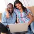Couple using laptop computer in their new house — Stock Photo #18222199