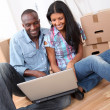 Couple using laptop computer in their new house — Stock Photo #18222205