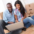 Couple using laptop computer in their new house - Stock Photo