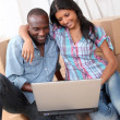 Couple using laptop computer in their new house — Stock Photo