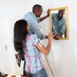 Young couple hanging mirror on the wall — Stock Photo #18222335