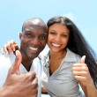 Cheerful couple showing thumbs up — Stock Photo