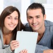 Couple sitting on sofa with electronic pad — Stock Photo #18223939