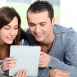 Stock Photo: Couple sitting on sofa with electronic pad