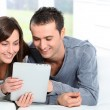 Couple sitting on sofa with electronic pad — Stock Photo #18223949