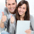 Young couple sitting on sofa with electronic pad — Stock Photo #18224027
