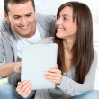 Young couple sitting on sofa with electronic pad — Stock Photo