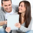 Stock Photo: Young couple sitting on sofa with electronic pad