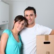Young couple carrying boxes into new house — Stock Photo