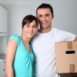 Young couple carrying boxes into new house — Stock Photo #18224533