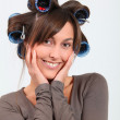Beautiful woman with hair-curlers doing funny faces — Stock Photo