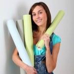 Beautiful young woman holding wallpaper rolls — Stock Photo
