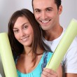 Royalty-Free Stock Photo: Closeup of young couple holding wallpaper rolls