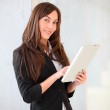 Businesswoman standing in hall with electronic pad — Stock Photo #18225217