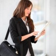 Businesswoman standing in hall with electronic pad — Stock Photo #18225223