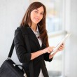Businesswoman standing in hall with electronic pad — Stock Photo #18225225