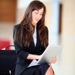 Businesswoman sitting in hall with electronic pad — Stock Photo #18225237