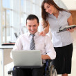 Royalty-Free Stock Photo: Businessman in wheelchair with assistant in office