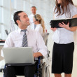Businessman in wheelchair with assistant in office — Stock Photo