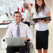 Businessman in wheelchair with assistant in office — Stock Photo #18225427