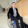 Businessmin wheelchair going to attend congress meeting — Stock Photo #18225431
