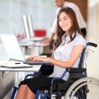 Businesswoman in wheelchair working in the office - Stok fotoğraf