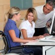 Woman in wheelchair working in the office — Stock Photo