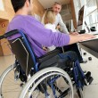 Man in wheelchair working in the office — Stock Photo #18225837