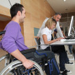Man in wheelchair working in the office — Stock Photo #18225851