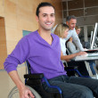 Man in wheelchair working in the office — Stock Photo